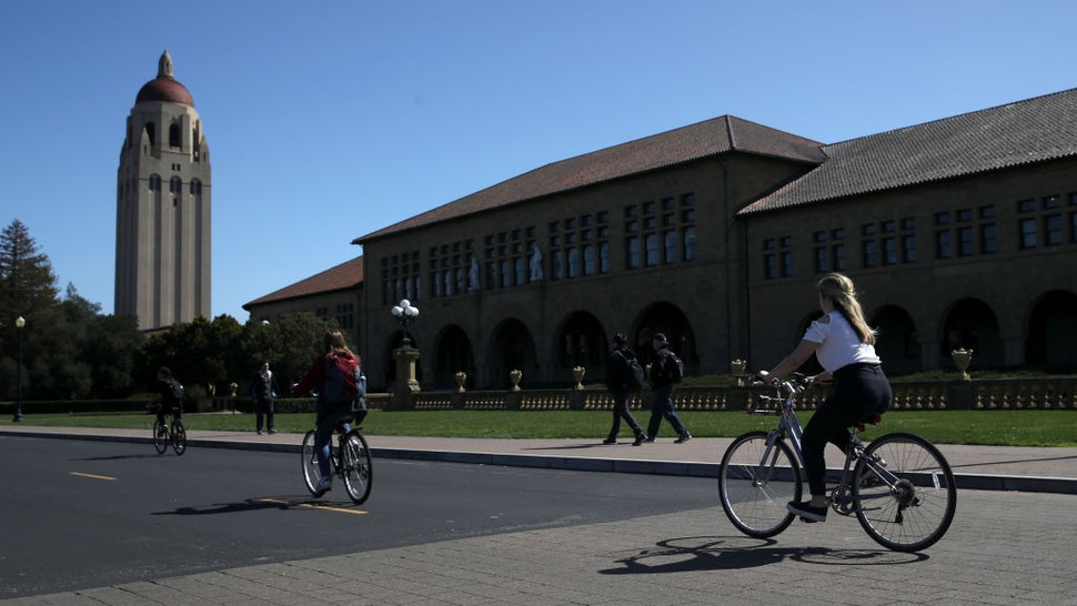 STANFORD, CA - MARCH 12: Cyclists ride by Hoover Tower on the Stanford University campus on March 12, 2019 in Stanford, California. More than 40 people, including actresses Lori Loughlin and Felicity Huffman, have been charged in a widespread elite college admission bribery scheme. Parents, ACT and SAT administrators and coaches at universities including Stanford, Georgetown, Yale, and the University of Southern California have been charged.