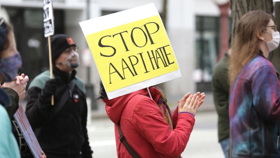 A demonstrator holds a sign calling for a stop to hate against Asian Americans and Pacific Islanders (AAPI) during a national day of action against anti-Asian violence in Seattle, Washington on March 27, 2021.
