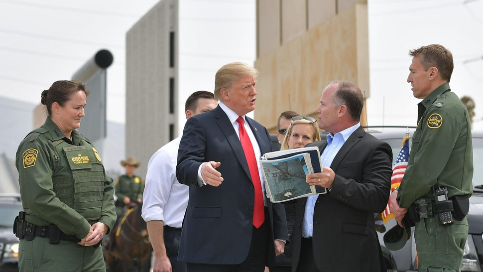 US President Donald Trump (C) is shown border wall prototypes in San Diego, California on March 13, 2018.