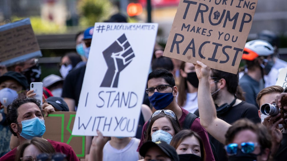 """MANHATTAN, NY - JUNE 14: A protester holds a homemade sign that says, """"I Stand With You #BlackLivesMatter"""" with a black power fist while another protester holds a sign that says, """"Supporting Trump Makes You Racist"""" in the middle of the crowd that gathered at Columbus Circle. This was part of the Warriors of the Garden Peaceful Protest Against President Donald Trump's 74th Birthday that started at Trump International Tower and drew large crowds. Protesters continue taking to the streets across America and around the world after the killing of George Floyd at the hands of a white police officer Derek Chauvin that was kneeling on his neck during for eight minutes, was caught on video and went viral. During his arrest as Floyd pleaded, """"I Can't Breathe"""". The protest are attempting to give a voice to the need for human rights for African American's and to stop police brutality against people of color. They are also protesting deep-seated racism in America. Many people were wearing masks and observing social distancing due to the coronavirus pandemic. Photographed in the Manhattan Borough of New York on June 14, 2020, USA."""