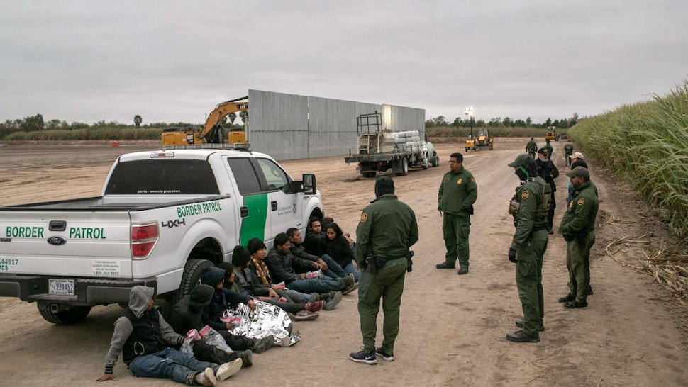 MISSION, TEXAS - DECEMBER 11: U.S. Border Patrol agents detain undocumented immigrants caught near a section of privately-built border wall under construction on December 11, 2019 near Mission, Texas. The hardline immigration group We Build The Wall is funding construction of the wall on private land along the Rio Grande, which forms the border with Mexico. The group, led by former Trump strategist Stephen Bannon claims to have raised tens of millions of dollars in a GoFundMe drive to build sections of wall along stretches of the U.S. southwest border with Mexico. (Photo by John Moore/Getty Images)