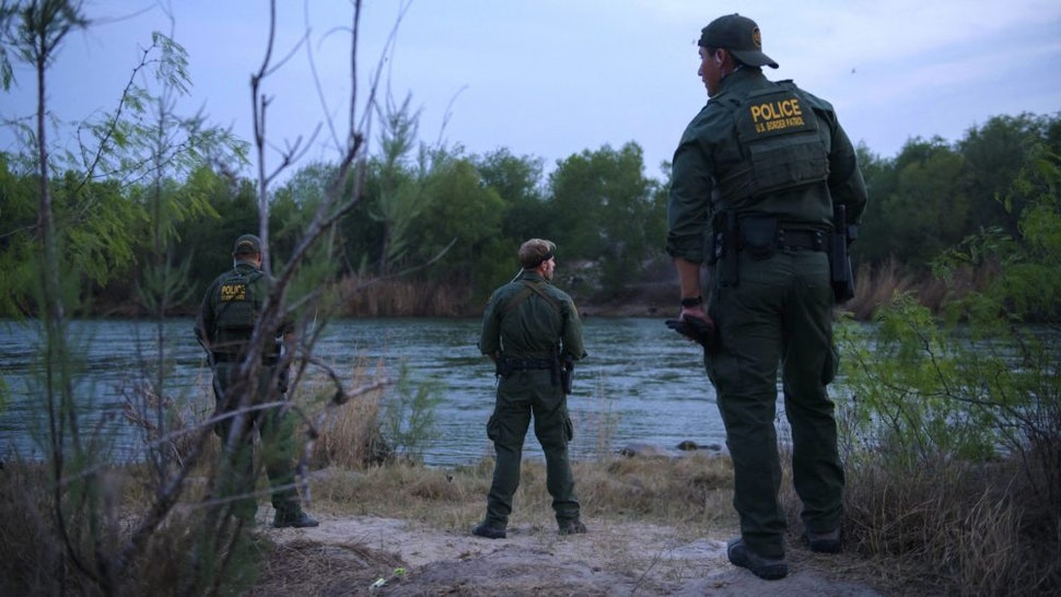 US border patrol agents stand on March 27, 2021 before the Rio Grande river that separates the US and Mexico, in the US border city of Roma.