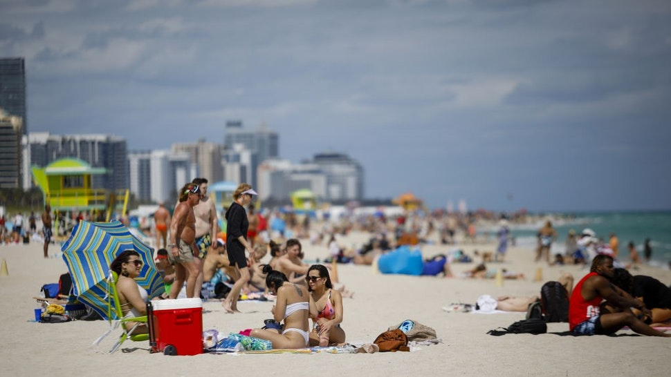 People gather on a beach in Miami, Florida, U.S., on Saturday, March 5, 2021. Even with some colleges canceling their mid-semester breaks, students from more than 200 schools are expected to visit Miami Beach during spring break, which runs from late February to mid-April. Photographer: