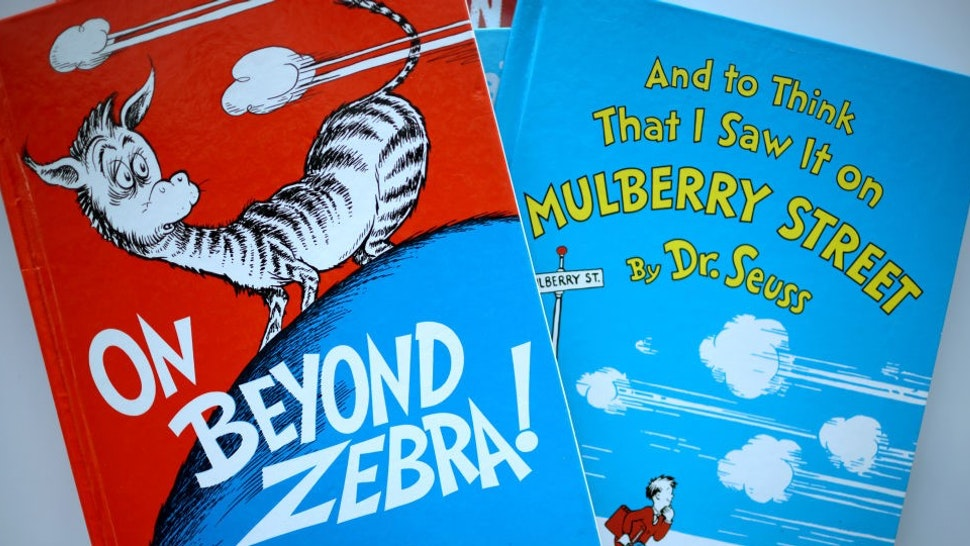"""CHICAGO, ILLINOIS - MARCH 02: Books by Theodor Seuss Geisel, aka Dr. Seuss, including """"On Beyond Zebra!"""" and """"And to Think That I Saw it on Mulberry Street,"""" are offered for loan at the Chinatown Branch of the Chicago Public Library on March 02, 2021 in Chicago, Illinois. The two titles are among six by the famed children's book author that will no longer be printed due to accusations of racist and insensitive imagery. The other titles include """"If I Ran the Zoo,"""" """"McElligot's Pool,"""" """"Scrambled Eggs Super!"""" and """"The Cat's Quizzer."""" (Photo Illustration by"""