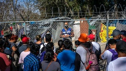 A worker with a nonprofit organization speaks with migrants as they prepare to cross the border into the United States in Matamoros, Tamaulipas state, Mexico, on Friday, Feb. 26, 2021. Emptying the camp in Matamoros would eliminate a symbol of Former U.S. President Donald Trump's immigration crackdown and count as an early success for Presidnt Biden, who aims to undo his predecessor's most draconian anti-immigrant policies.