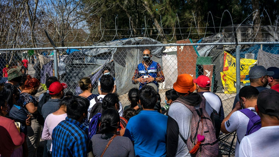 A worker with a nonprofit organization speaks with migrants as they prepare to cross the border into the United States in Matamoros, Tamaulipas state, Mexico, on Friday, Feb. 26, 2021. Emptyingthe camp inMatamoroswould eliminatea symbol of Former U.S. President Donald Trump'simmigration crackdown and count as an early successfor Presidnt Biden, who aimsto undo his predecessor'smost draconian anti-immigrant policies.