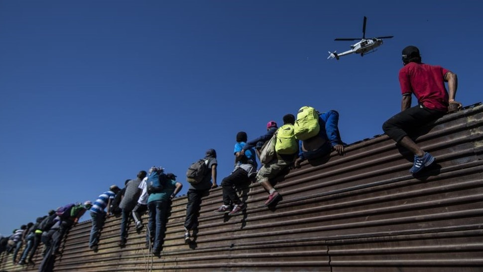 """TOPSHOT - A group of Central American migrants -mostly Hondurans- climb a metal barrier on the Mexico-US border near El Chaparral border crossing, in Tijuana, Baja California State, Mexico, on November 25, 2018. - US officials closed the San Ysidro crossing point in southern California on Sunday after hundreds of migrants, part of the """"caravan"""" condemned by President Donald Trump, tried to breach a fence from Tijuana, authorities announced. (Photo by Pedro PARDO / AFP) (Photo credit should read"""