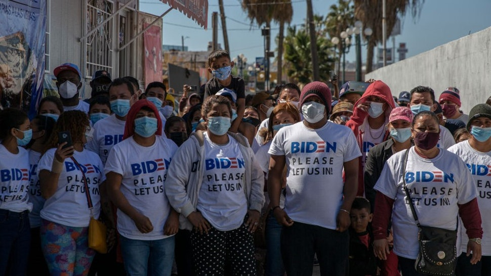 """02 March 2021, Mexico, San Ysidro: """"Biden, please let us in,"""" reads in English on the T-shirts of a group of migrants from different backgrounds who made their way to the """"El Chaparral"""" international border crossing. The migrants were asking the new U.S. government for asylum. U.S. Border Patrol (CPB) agents conducted a heavier operation at the border crossing with the goal of preventing an onslaught. Photo: Stringer/dpa (Photo by"""