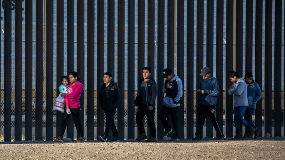 CIUDAD JUAREZ, MEXICO - MARCH 17: Undocumented immigrants walk along the U.S.-Mexico border wall after they ran across the shallow Rio Grande into El Paso on March 17, 2021 in Ciudad Juarez, Mexico. U.S. immigration officials are dealing with an immigrant surge along the southwest border with Mexico. (Photo by