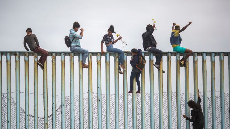 TIJUANA, MEXICO - APRIL 29: People climb a section of border fence to look toward supporters in the U.S. as members of a caravan of Central American asylum seekers arrive to a rally on April 29, 2018 in Tijuana, Baja California Norte, Mexico. More than 300 immigrants, the remnants of a caravan of Central Americans that journeyed across Mexico to ask for asylum in the United States, have reached the border to apply for legal entry. (Photo by