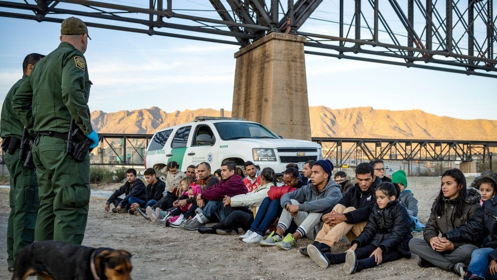 """TOPSHOT - A group of about 30 Brazilian migrants, who had just crossed the border, sit on the ground near US Border Patrol agents, on the property of Jeff Allen, who used to run a brick factory near Mt. Christo Rey on the US-Mexico border in Sunland Park, New Mexico on March 20, 2019. - The militia members say they will patrol the US-Mexico border near Mt. Christo Rey, """"Until the wall is built."""" In recent months, thousands of Central Americans have arrived in Mexico in several caravans in the hope of finding a better life in the United States. US President Donald Trump has branded such migrants a threat to national security, demanding billions of dollars from Congress to build a wall on the southern US border. (Photo by"""