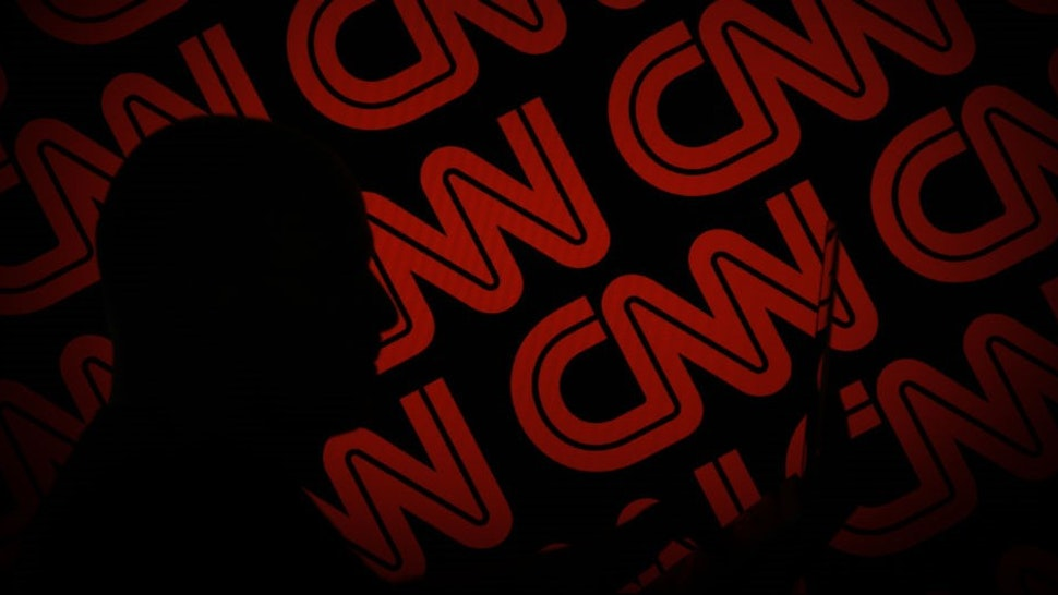 A man is seen holding with a smart device in front of a CNN logo in this photo illustration on 2 July, 2017. (Photo by