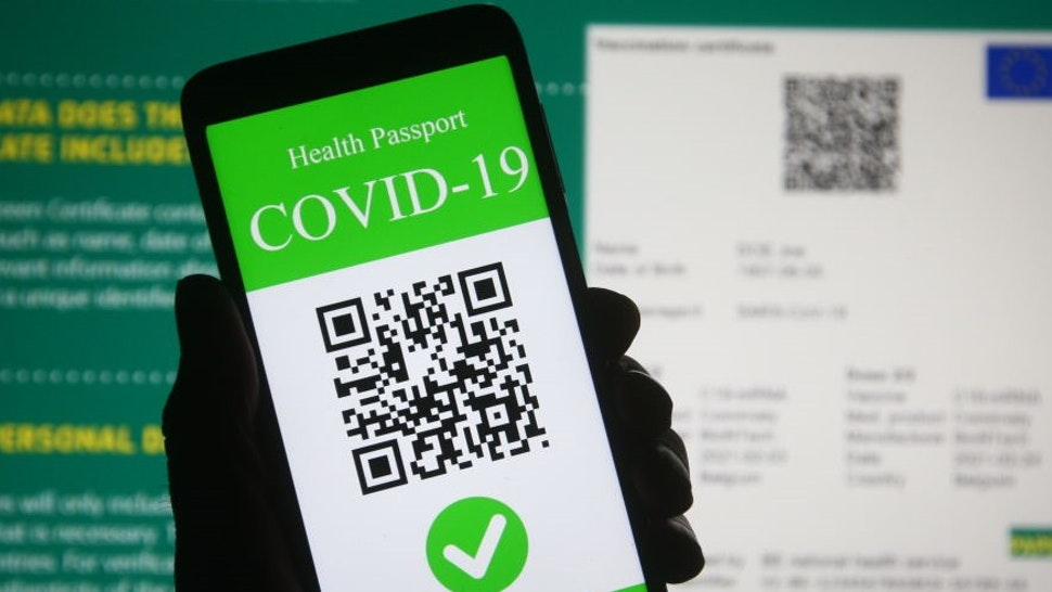 UKRAINE - 2021/03/28: In this photo illustration, a symbolic COVID-19 health passport seen displayed on a smartphone screen in front of the European Commission information about a proposal to create a Digital Green Certificate. On March 17 the European Commission presented a proposal to create a Digital Green Certificate to facilitate the safe free movement of the EU citizens during the COVID-19 pandemic. (Photo Illustration by