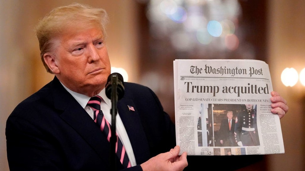 WASHINGTON, DC - FEBRUARY 06: U.S. President Donald Trump holds a copy of The Washington Post as he speaks in the East Room of the White House one day after the U.S. Senate acquitted on two articles of impeachment, ion February 6, 2020 in Washington, DC. After five months of congressional hearings and investigations about President Trump's dealings with Ukraine, the U.S. Senate formally acquitted the president on Wednesday of charges that he abused his power and obstructed Congress. (Photo by
