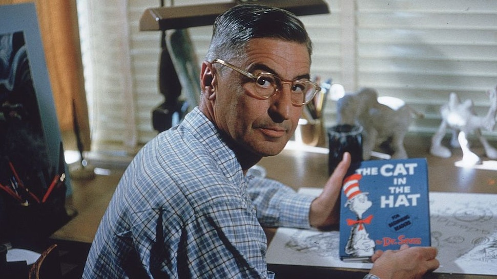 American author and illustrator Dr Seuss (Theodor Seuss Geisel, 1904 - 1991) sits at his drafting table in his home office with a copy of his book, 'The Cat in the Hat', La Jolla, California, April 25, 1957. (Photo by