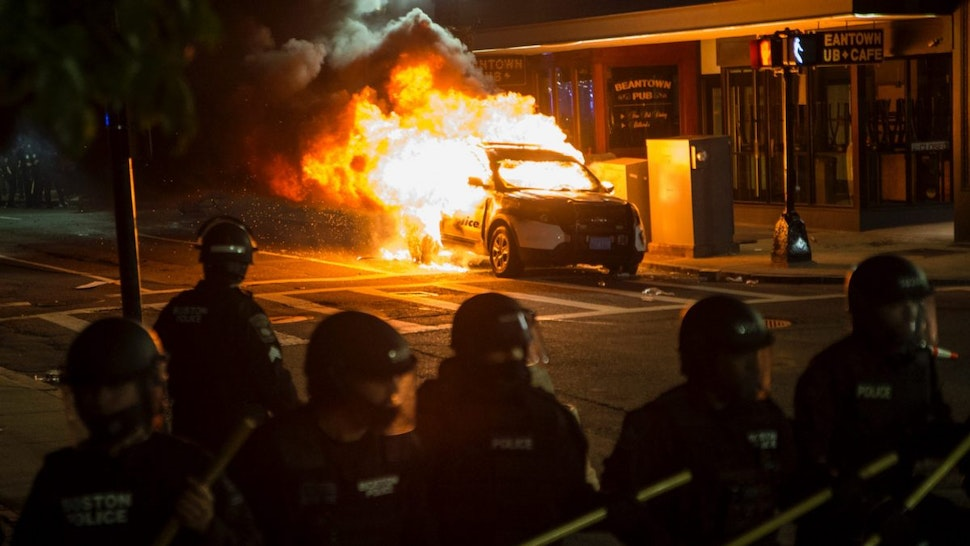 A police cruiser burns behind the Police line near the intersection of Park and Tremont as a protest against police brutality pushes through the streets of Boston on May 31, 2020.