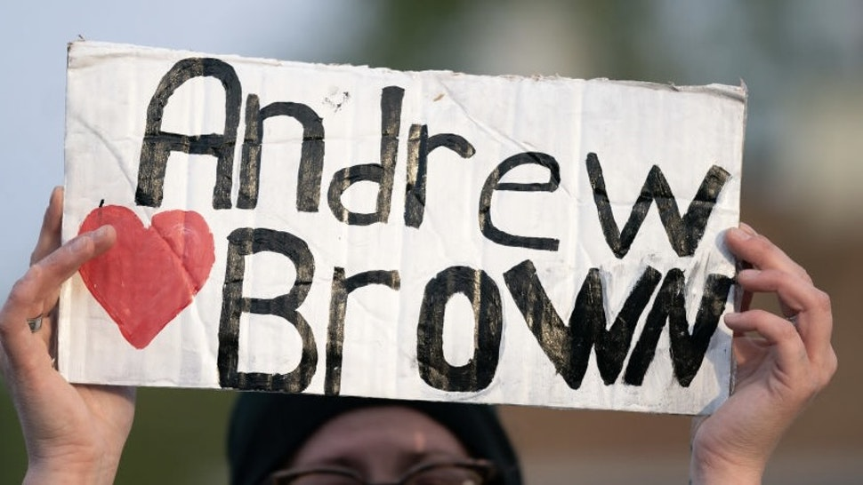 ELIZABETH CITY, NC - APRIL 22: A demonstrator holds a sign for Andrew Brown Jr. during a protest march on April 22, 2021 in Elizabeth City, North Carolina. The protest was sparked by the police killing of Brown on April 21. (Photo by Sean Rayford/Getty Images)