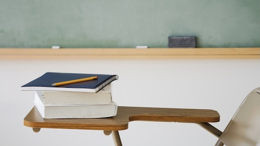 Books and pencil on desk in classroom - stock photo
