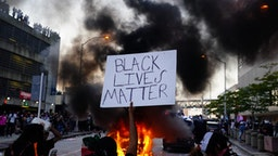 29: A man holds a Black Lives Matter sign as a police car burns during a protest on May 29, 2020 in Atlanta, Georgia.