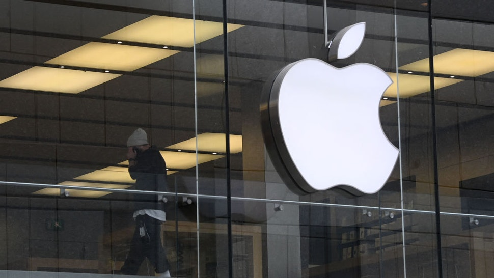 """The logo of US tech giant Apple can be seen on an Apple store in Munich, southern Germany. - Apple said it planned to invest more than one billion euros ($1.2 billion) in Germany and open Europe's biggest research facility on mobile wireless semiconductors and software. The company said it would make Munich its """"European Silicon Design Centre"""", creating hundreds of new jobs at a facility for 5G and wireless technologies."""