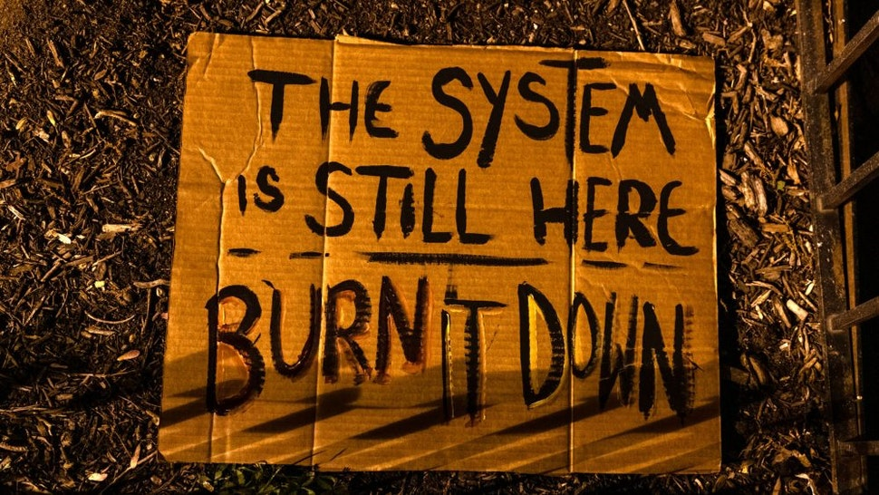 """A sign reading """"The system is still here. Burn it down."""" at Black Lives Matter Plaza in Washington, D.C., U.S., on Tuesday, April 20, 2021. Former Minneapolis police officer Derek Chauvin was found guilty of killingGeorge Floydwhen he knelt on the mans neck for 9 minutes and 29 seconds, a videotaped death that ignited a summer of rage and the greatest racial reckoning in the U.S. since the 1960s."""