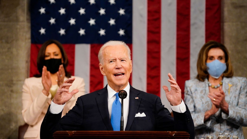 WASHINGTON, DC - APRIL 28: President Joe Biden addresses a joint session of Congress, with Vice President Kamala Harris and House Speaker Nancy Pelosi (D-CA) on the dais behind him on April 28, 2021 in Washington, DC. On the eve of his 100th day in office, Biden spoke about his plan to revive America's economy and health as it continues to recover from a devastating pandemic. He delivered his speech before 200 invited lawmakers and other government officials instead of the normal 1600 guests because of the ongoing COVID-19 pandemic.