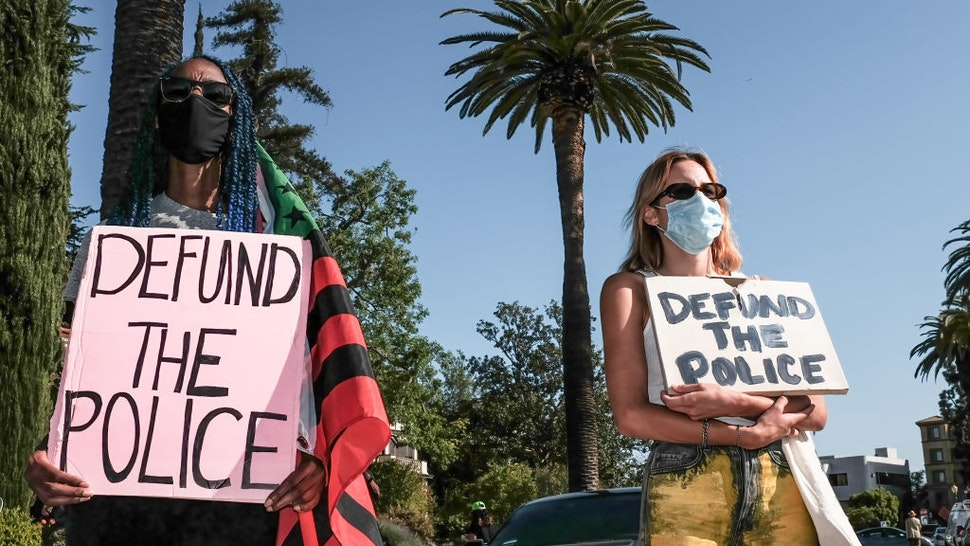 LOS ANGELES, CALIFORNIA, UNITED STATES - 2021/04/20: Protesters hold placards during the demonstration. Hours after the verdict of the Derek Chauvin trial, protesters meet outside of Los Angeles Mayor Eric Garcetti's home to protest his proposed funding of the Los Angeles Police Department.