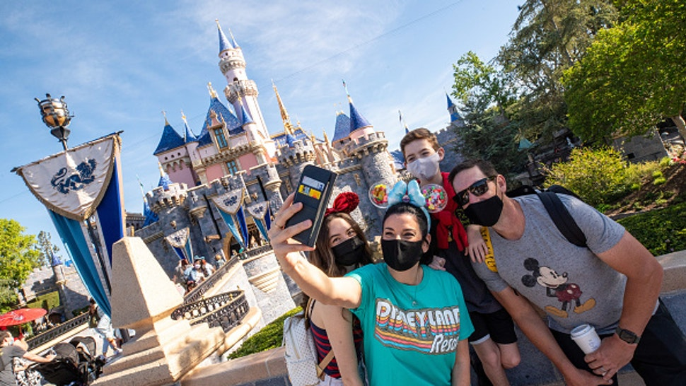 ANAHEIM, CA - APRIL 30: In this handout photo provided by Disneyland Resort, The Wotter family of Lake Elsinore, California, takes a selfie photo in front of Sleeping Beauty Castle as Disneyland Park at the Disneyland Resort on April 30, 2021 in Anaheim, California. Guests are being welcomed back as Disneyland Park, Disney California Adventure Park and Disney's Grand Californian Hotel & Spa are reopening