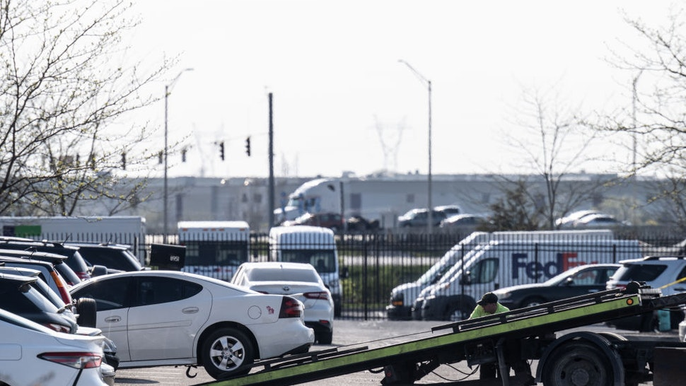 INDIANAPOLIS, IN - APRIL 16: A tow truck driver begins to move a vehicle involved in the crime scene within the parking lot of a FedEx Ground facility on April 16, 2021 in Indianapolis, Indiana. The area is the scene of a mass shooting at FedEx Ground Facility that left at least eight people dead and five wounded on the evening of April 15. Police have identified the suspect as former FedEx employee, Brandon Scott Hole, who died of an apparent self-inflicted gunshot wound after the shooting.
