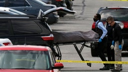 """Officials load a body into a vehicle at the site of a mass shooting at a FedEx facility in Indianapolis, Indiana, on April 16, 2021. - A gunman has killed at least eight people at the facility before turning the gun on himself in the latest in a string of mass shootings in the country, authorities said. The incident came a week after President Joe Biden branded US gun violence an """"epidemic"""" and an """"international embarrassment"""" as he waded into the tense debate over gun control, a powerful political issue in the US. (Photo by Jeff Dean / AFP)"""