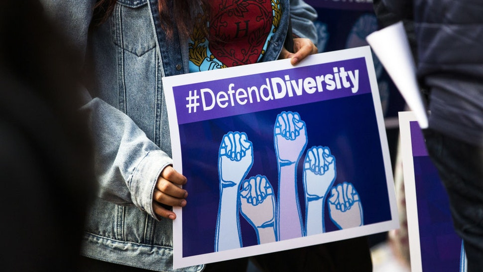 """A demonstrator supporting Harvard University's admission process holds a sign that reads """"Defend Diversity"""" during a protest outside of the Massachusetts Bay Transportation Authority (MBTA) Harvard station in Cambridge, Massachusetts, U.S., on Sunday, Oct. 14, 2018. Harvard University was sued by a group that claims their law school illegally used race and gender as criteria for selecting law students to staff their most elite academic journals, a suit that comes amid growing scrutiny of affirmative action in college admissions."""