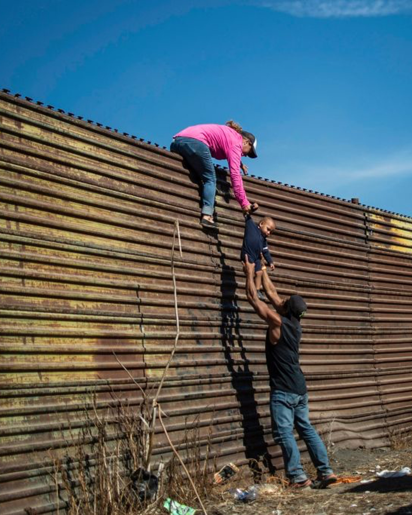 TOPSHOT - A group of Central American migrants climb the border fence between Mexico and the United States, near El Chaparral border crossing, in Tijuana, Baja California State, Mexico, on November 25, 2018. - Hundreds of migrants attempted to storm a border fence separating Mexico from the US on Sunday amid mounting fears they will be kept in Mexico while their applications for a asylum are processed. An AFP photographer said the migrants broke away from a peaceful march at a border bridge and tried to climb over a metal border barrier in the attempt to enter the United States. (Photo by Pedro PARDO / AFP) (Photo by PEDRO PARDO/AFP via Getty Images)