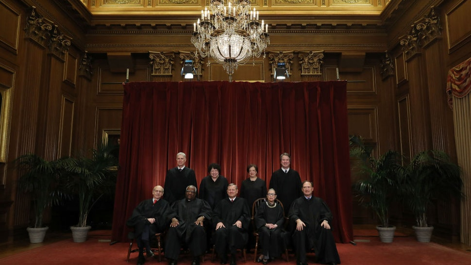 """WASHINGTON, DC - NOVEMBER 30: United States Supreme Court (Front L-R) Associate Justice Stephen Breyer, Associate Justice Clarence Thomas, Chief Justice John Roberts, Associate Justice Ruth Bader Ginsburg, Associate Justice Samuel Alito, Jr., (Back L-R) Associate Justice Neil Gorsuch, Associate Justice Sonia Sotomayor, Associate Justice Elena Kagan and Associate Justice Brett Kavanaugh pose for their official portrait at the in the East Conference Room at the Supreme Court building November 30, 2018 in Washington, DC. Earlier this month, Chief Justice Roberts publicly defended the independence and integrity of the federal judiciary against President Trump after he called a judge who had ruled against his administration's asylum policy """"an Obama judge."""" """"We do not have Obama judges or Trump judges, Bush judges or Clinton judges,"""" Roberts said in a statement. """"What we have is an extraordinary group of dedicated judges doing their level best to do equal right to those appearing before them. That independent judiciary is something we should all be thankful for."""" (Photo by Chip Somodevilla/Getty Images)"""