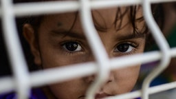 """TOPSHOT - A girl waits to be given asylum or a humanitary visa at the immigration office on the Mexico-Guatemala international bridge in Ciudad Hidalgo, Chiapas State, Mexico, on June 6, 2019. - The US warned Mexico Thursday it needed to make more concessions on slowing migration to avoid President Donald Trump's threatened tariffs, as the Mexican leader announced he would visit the border to """"defend our dignity."""" Mexican authorities responded to one key US demand Wednesday by blocking the latest US-bound caravan of undocumented migrants as it entered Mexico from Guatemala."""