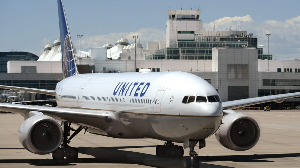 DENVER, COLORADO - JUNE 20, 2019: A United Airlines Boeing 777 passenger aircraft taxis into its gate at Denver International Airport in Denver, Colorado.