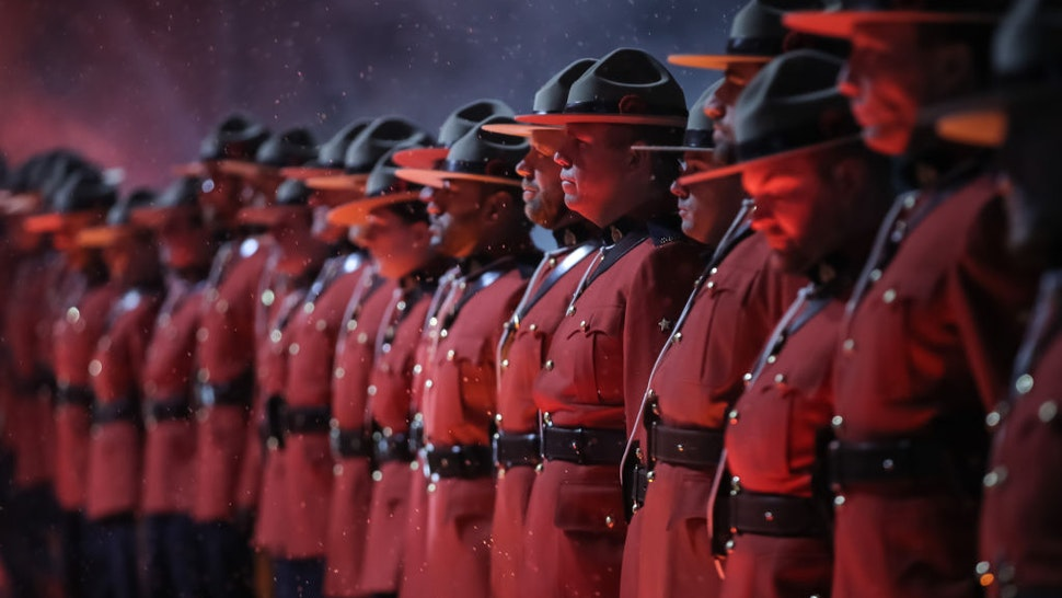 Uniformed Royal Canadian Mounted Police officers line up in a Wall of Honour before the Calgary Flames take on the Winnipeg Jets during the 2019 Tim Hortons NHL Heritage Classic at Mosaic Stadium on October 26, 2019 in Regina, Saskatchewan, Canada