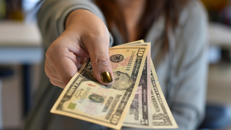 Midsection Of Woman Giving Paper Currency - stock photo