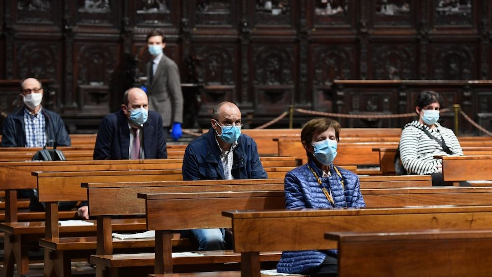 People attend a mass at the Cappella Feriale chapel of the Duomo cathedral in Milan on May 18, 2020 during the country's lockdown aimed at curbing the spread of the COVID-19 infection, caused by the novel coronavirus. - Restaurants and churches reopen in Italy on May 18, 2020 as part of a fresh wave of lockdown easing in Europe and the country's latest step in a cautious, gradual return to normality, allowing businesses and churches to reopen after a two-month lockdown. (Photo by Miguel MEDINA / AFP) (Photo by MIGUEL MEDINA/AFP via Getty Images)