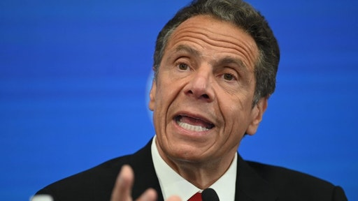 Governor of New York Andrew Cuomo speaks during a press conference at the New York Stock Exchange (NYSE) on May 26, 2020 at Wall Street in New York City. - The New York Stock Exchange, the symbolic heart of Wall Street, reopened its floor Tuesday after a two-month closure due to the coronavirus, with traders donning masks and separated by plexiglas.Stocks surged at the outset of the session following the trademark opening bell, which was presided by New York Governor Andrew Cuomo and NYSE officials -- all donning masks.