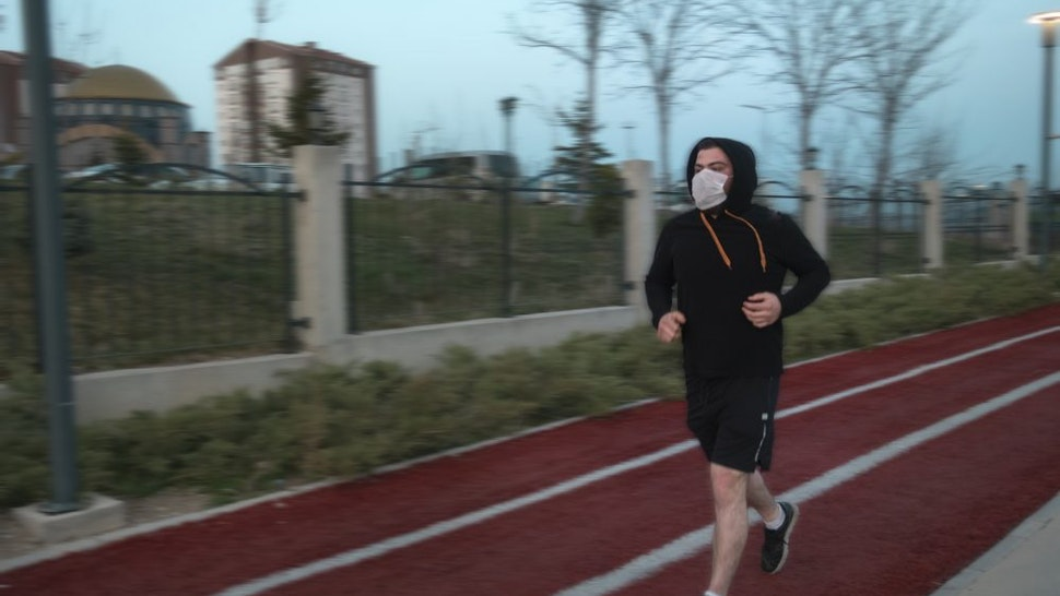 Isolated young man wearing mask and a hoodie running at a parkIsolated young man wearing mask and a hoodie running at a park