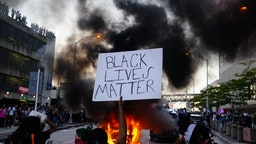 ATLANTA, GA - MAY 29: A man holds a Black Lives Matter sign as a police car burns during a protest on May 29, 2020 in Atlanta, Georgia. Demonstrations are being held across the US after George Floyd died in police custody on May 25th in Minneapolis, Minnesota. (Photo by Elijah Nouvelage/Getty Images)