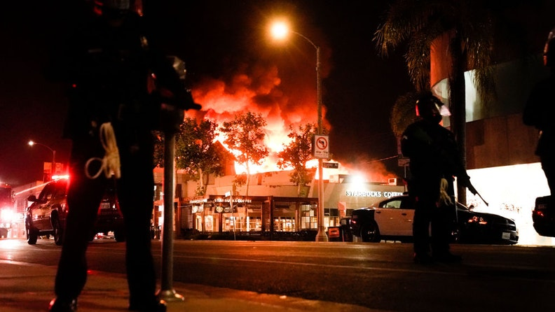 Law enforcement officers with a structure ablaze int he background in the Fairfax District on Saturday, May 30, 2020 in Los Angeles, CA.
