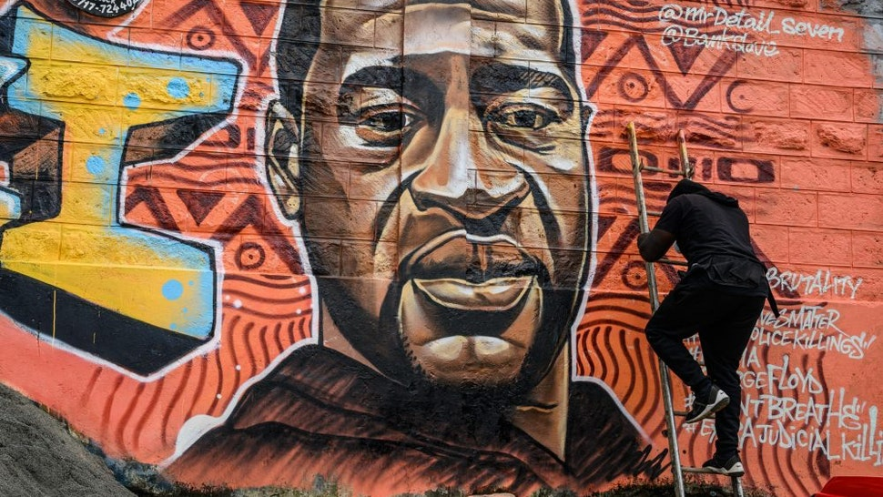 Kenyan mural artist Allan Mwangi, also known as Mr.detail.seven, paints a graffiti mural in the Kibera slum in Nairobi on June 3, 2020, depicting the American, George Floyd, who was killed by a police officer in Minneapolis, in the United States.