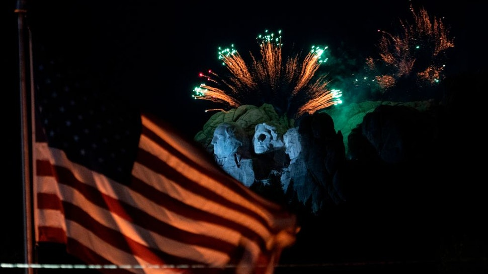 A US flag flies as fireworks explode above the Mount Rushmore National Monument during an Independence Day event attended by the US president in Keystone, South Dakota, July 3, 2020