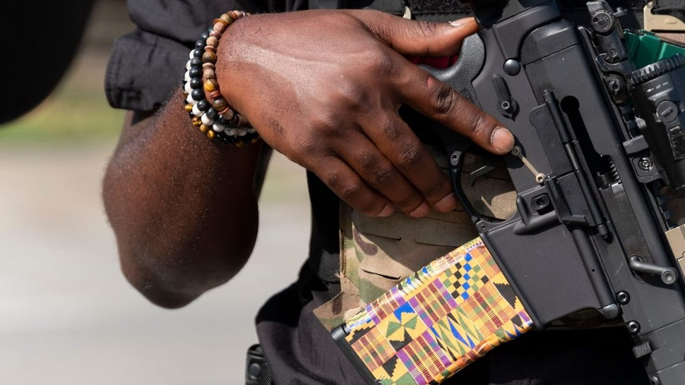 """EDITORS NOTE: Graphic content / A member of the """"Not Fucking Around Coalition"""" (NFAC), an all Black militia, holds a weapon during a rally to protest the killing of Breonna Taylor, in Louisville, Kentucky on July 25, 2020."""