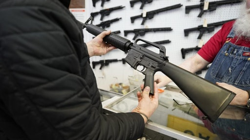 A salesperson shows an AR-15 rifle to a customer at a store in Orem, Utah, U.S., on Thursday, March 25, 2021. Two mass shootings in one week are giving Democrats new urgency to pass gun control legislation, but opposition from Republicans in the Senate remains the biggest obstacle to any breakthrough in the long-stalled debate.