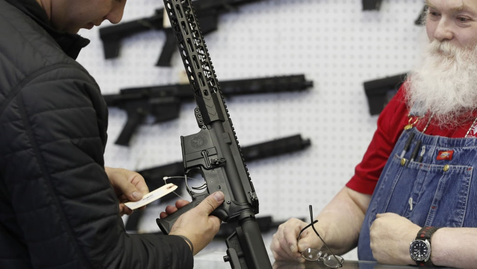 A salesperson shows an AR-15 rifle to a customer at a store in Orem, Utah, U.S., on Thursday, March 25, 2021. Two mass shootings in one week are giving Democrats new urgency to pass gun control legislation, but opposition from Republicans in the Senate remains the biggest obstacle to any breakthrough in the long-stalled debate. Photographer: