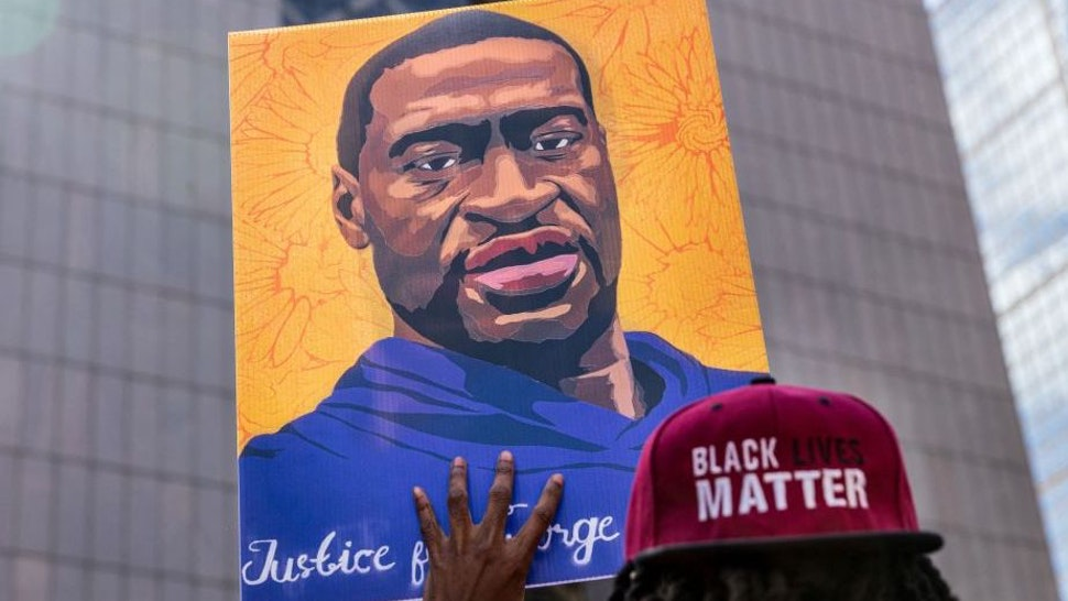 Demonstrators hold signs honouring George Floyd and other victims of racism as they gather during a protest outside Hennepin County Government Center on March 28, 2021 in Minneapolis, Minnesota.