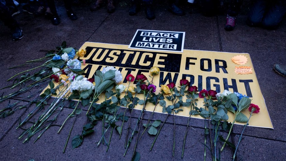 People lay flowers on a sign as they rally outside the Brooklyn Center police station to protest the death of Daunte Wright who was shot and killed by a police officer in Brooklyn Center, Minnesota on April 13, 2021. - Tensions have soared over the death on April 11 of African American Daunte Wright near the Midwestern US city, a community already on edge over the ongoing trial of a policeman accused of killing another Black man, George Floyd. (Photo by Kerem YUCEL / AFP) (Photo by KEREM YUCEL/AFP via Getty Images)