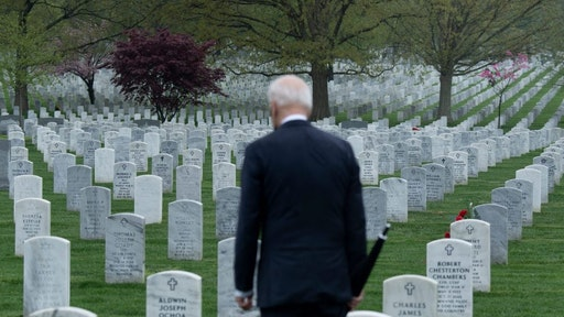 "TOPSHOT - US President Joe Biden walks through Arlington National cemetary to honor fallen veterans of the Afghan conflict in Arlington, Virginia on April 14, 2021. - President Joe Biden announced it's ""time to end"" America's longest war with the unconditional withdrawal of troops from Afghanistan, where they have spent two decades in a bloody, largely fruitless battle against the Taliban."
